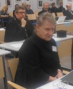 Kirkolliskokousedustaja Anja Lindström. Taustalla Helsingin seurakunnan kirkkoherra isä Markku Salminen.