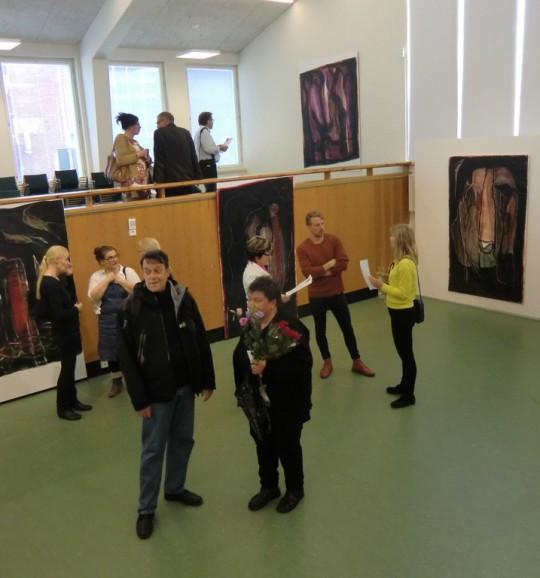 Soili Talja ottaa vastaan jatkuvana virtana saapuvia avajaisvieraita. Oikealla teos Liljojen luola (2014), eräs taiteilijalle itselleen hyvin läheinen työ. Vasemmalla näkyvät osittain omat ehdottomat suosikkini Mirhantuojat II (1914) ja Mirhantuojat III (2015) (Kuva/Photo: Hellevi Matihalti)