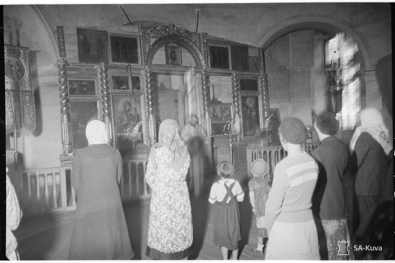 """""""Vepsänmaan kirkot ovat avanneet ovensa ja kristityt vepsäläiset saavat jälleen palvella jumalaansa rakkaissa temppeleissään, jotka olivat bolsevikkivallan aikana muutetut tanssisaleiksi ja vilja-aitoiksi. Soutjärvi, Mäkikylä 1943.06.26"""" (Kuva/Photo: SA-kuva )"""