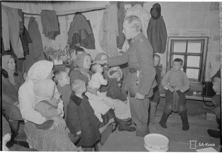 """""""Ristiäiset. Nuori kenttäpappi siunaa karjalaisessa tuvassa ristittäviä lapsia. Paateneen kauppala 1941.11.21"""" (Kuva/Photo: SA-Kuva )"""