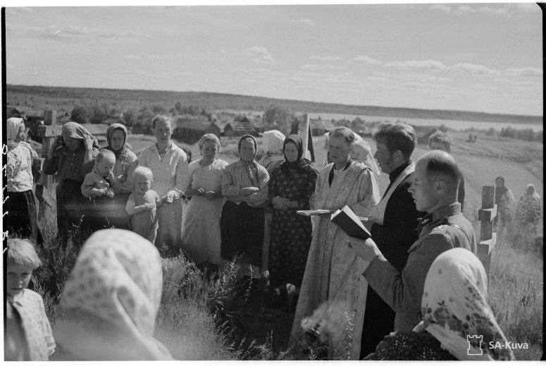 """""""Juhannuspäivänä on myöskin surujuhla vepsäläiskylässä, bolsevikkivallan aikana kuolleet on täytynyt haudata siunaamattomina. Nyt on pappi saapunut kylään ja siunaus voidaan suorittaa. Soutjärvi, Metsäntaka 1943.06.24"""" (Kuva/Photo: SA-kuva)"""