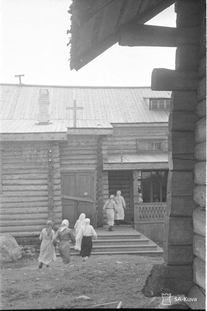 """""""Kirkkoväkeä matkalla ensimmäiseen jumalanpalvelukseen, entiseen klubitaloon, josta nyttemmin on tehty kirkko. Vieljärvi 1941.08.24"""" (Kuva/Photo: SA-kuva)"""