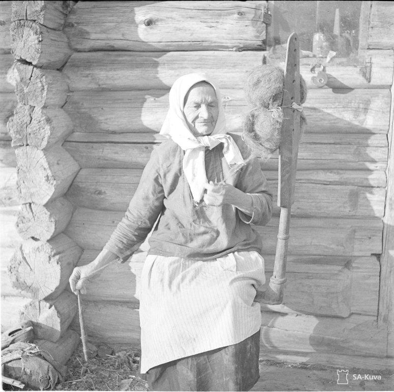 """""""Karjalainen Ondrio Maria Pedrovna, 85-vuotias, kehrää värttinällä. Ei suostunut lähtemään ryssien mukana vaan piilottautui. Veskelys 1941.09.10"""" (Kuva/Photo:SA-kuva)"""