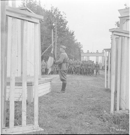 """""""Paraati: Itä-Karjalan lippu nousee salkoon. Aunus 1941.09.10"""" Itä-Karjalan miehitysalueella käytettiin Itä-Karjalan omaa lippua rinnan Suomen lipun kanssa. (Kuva/Photo: SA-kuva)"""
