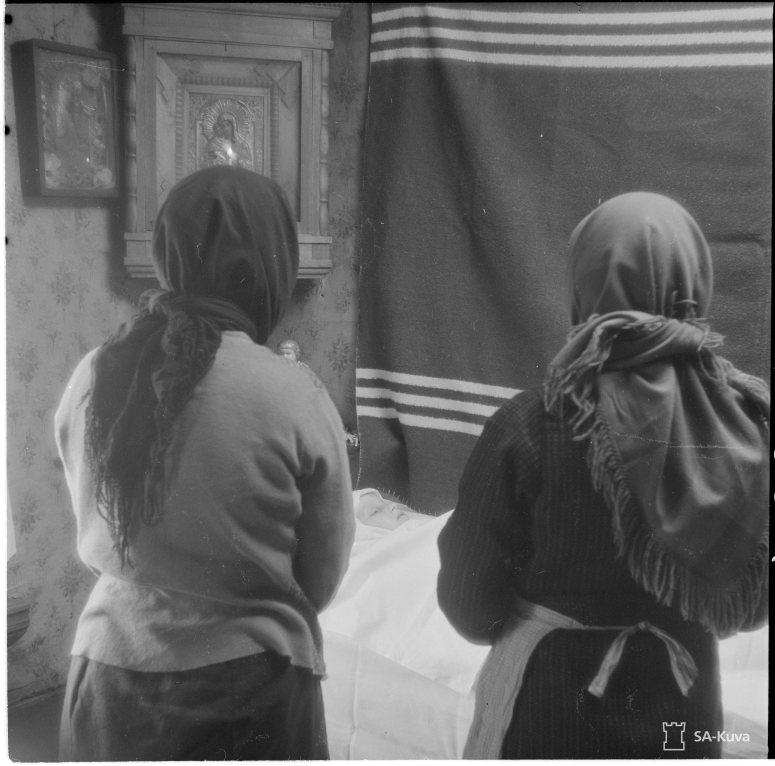 """""""Nurmoilan pommituksessa 1.5.1942 kuoli 2 naapuritalojen pikkutyttöä, toinen 9v Dunja, toinen 11 v Anni. Heidät haudattiin samana päivänä 3.5. Nurmoilan kalmistoon: Dunja makaa paareillaan kotonaan. Ikonin edessä palaa kynttilä, ikonin alla olevalla nurkkapöydällä ovat Dunjan lelut. Ruumiin vieressä ovat äiti ja perheen 8:sta lapsesta ainoa elossa oleva tytär. Nurmoila 1942.05.03"""" (Kuva/Photo: SA-kuva)"""