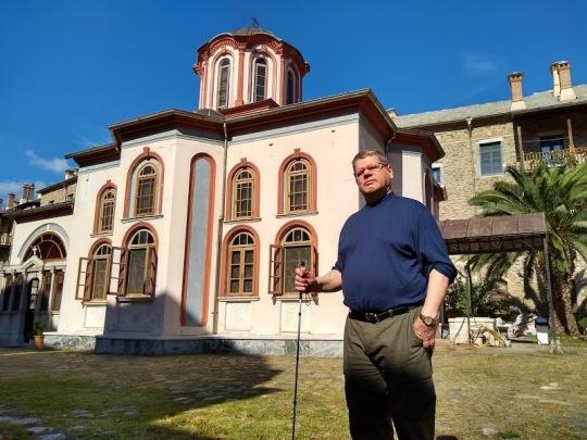 Timo Lehtonen seisoo Iviroin luostarin kirkon edessä, aurinko paistaa.