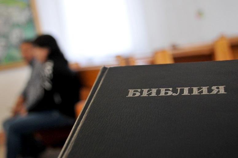 Venäjänkielinen Raamattu. Taustalla ihmishahmo.